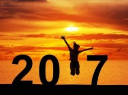 Silhouette young woman jumping on the sea and 2017 years while celebrating new year, happy victory and success concept.